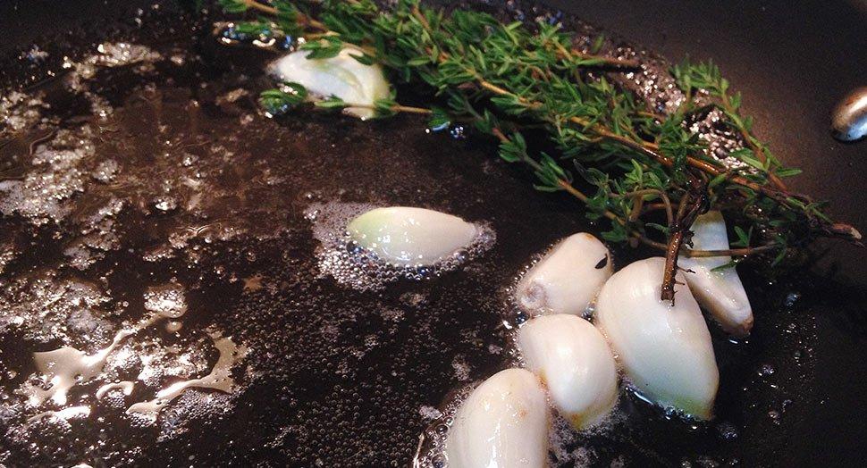 Приготовление чеснока и тимьяна для стейка с беконом, сыром, грибами и луком. Изображение brodude